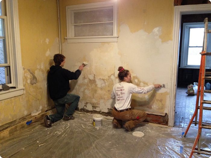 Courtesy of Hannah Wolfrum | Wolfram spackles the dining room wall with the help of a friend.